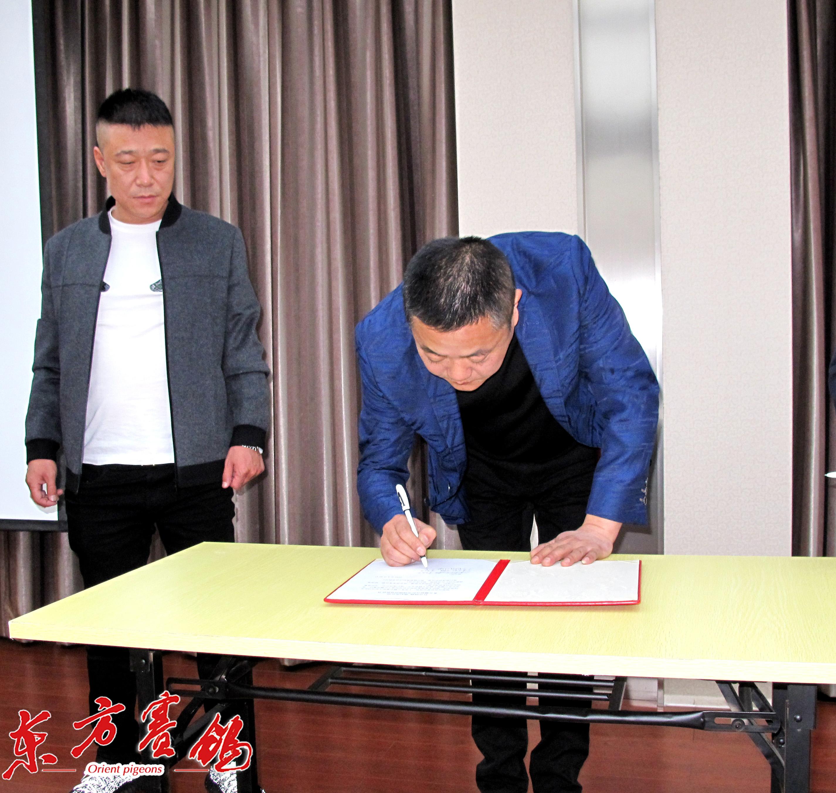 12、天津卓翔公棚董事长王军-右、天津彪行天下公棚姜荗旺-左,在打击网鸽活动协议书上签字。