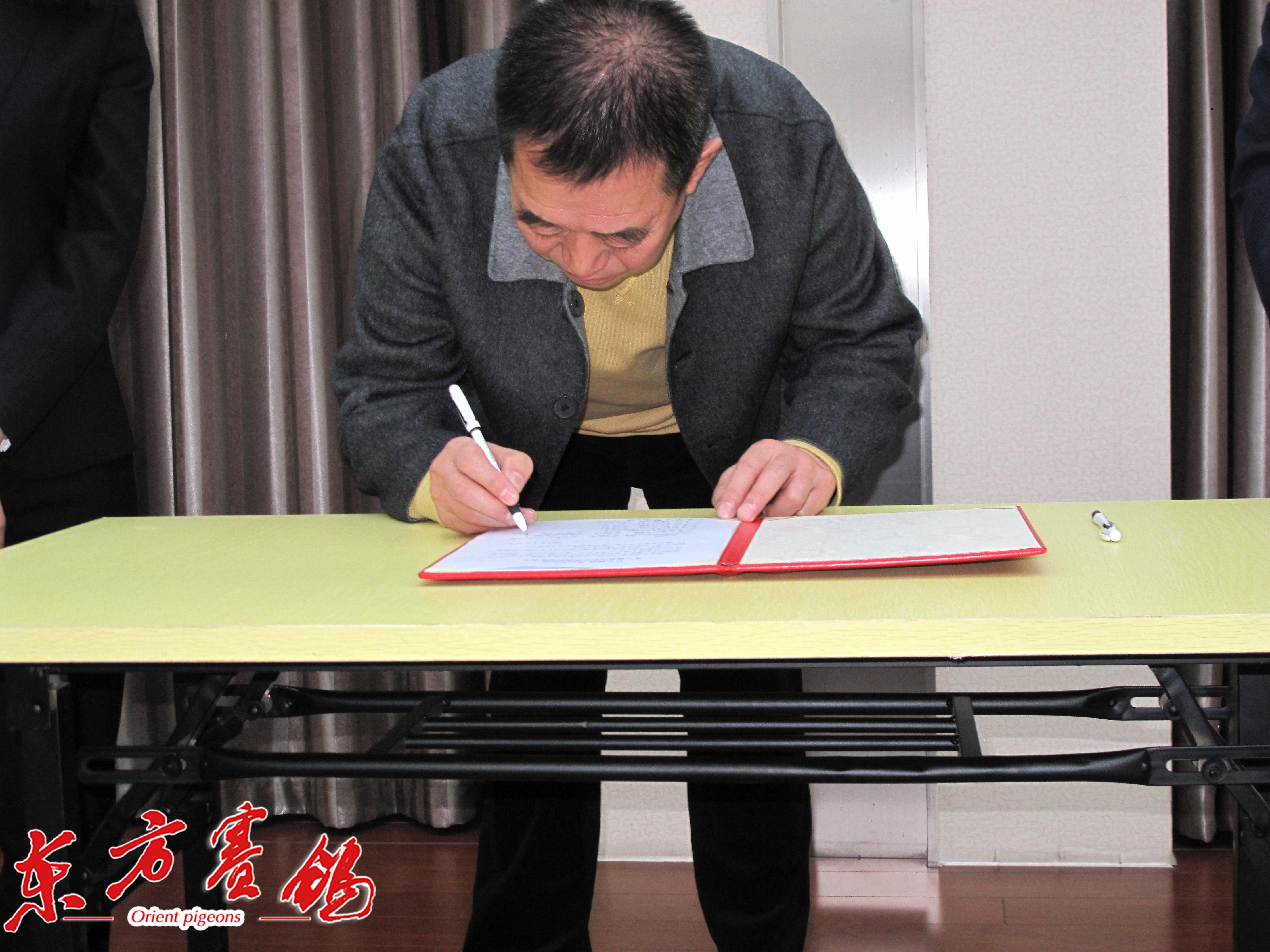 15、天津市信鸽协会主席李国玺在打击网鸽协议书上签字。
