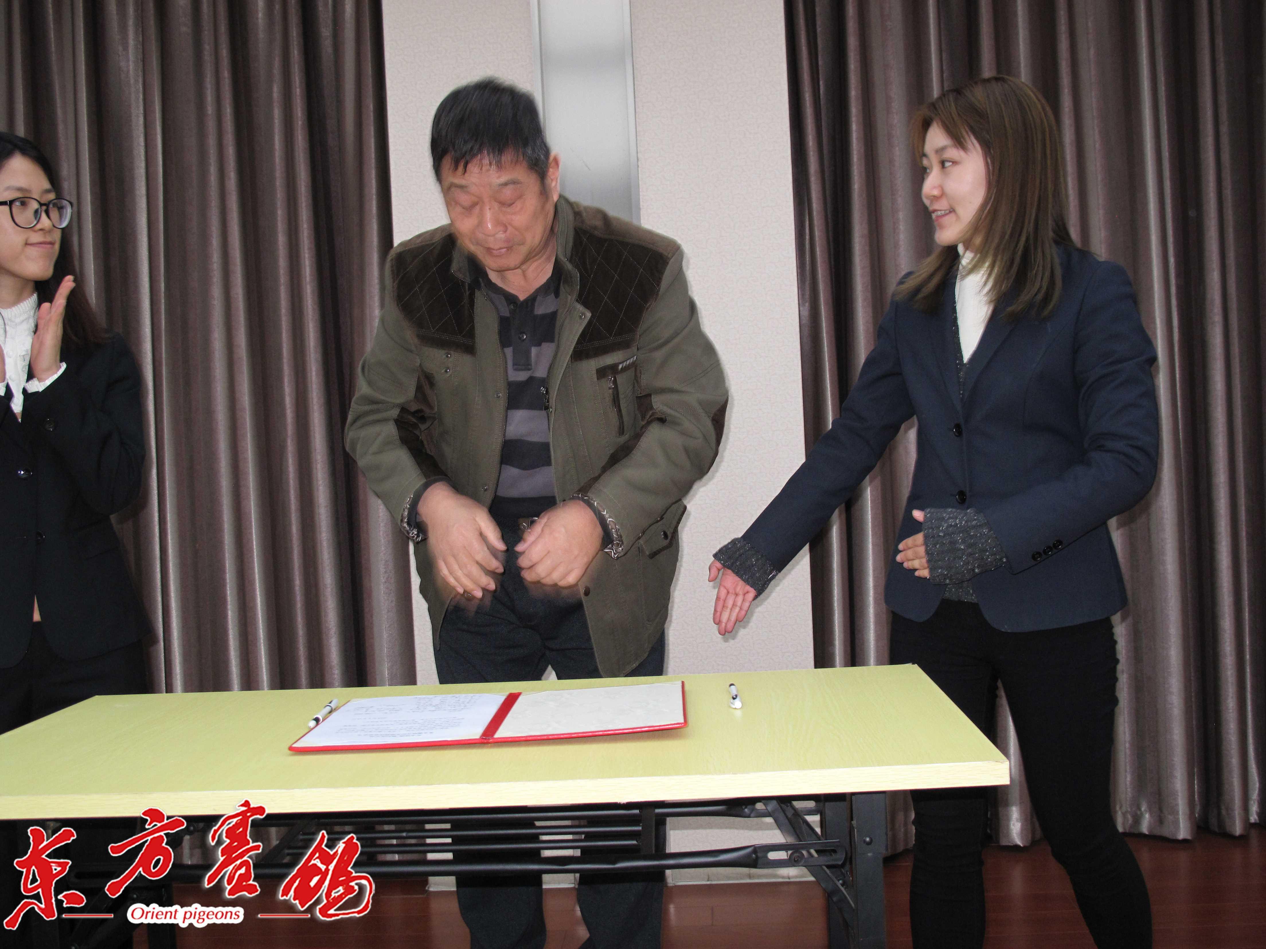 18、天津市信鸽协会副主席贾福利在打击网鸽活动协议书上签字。