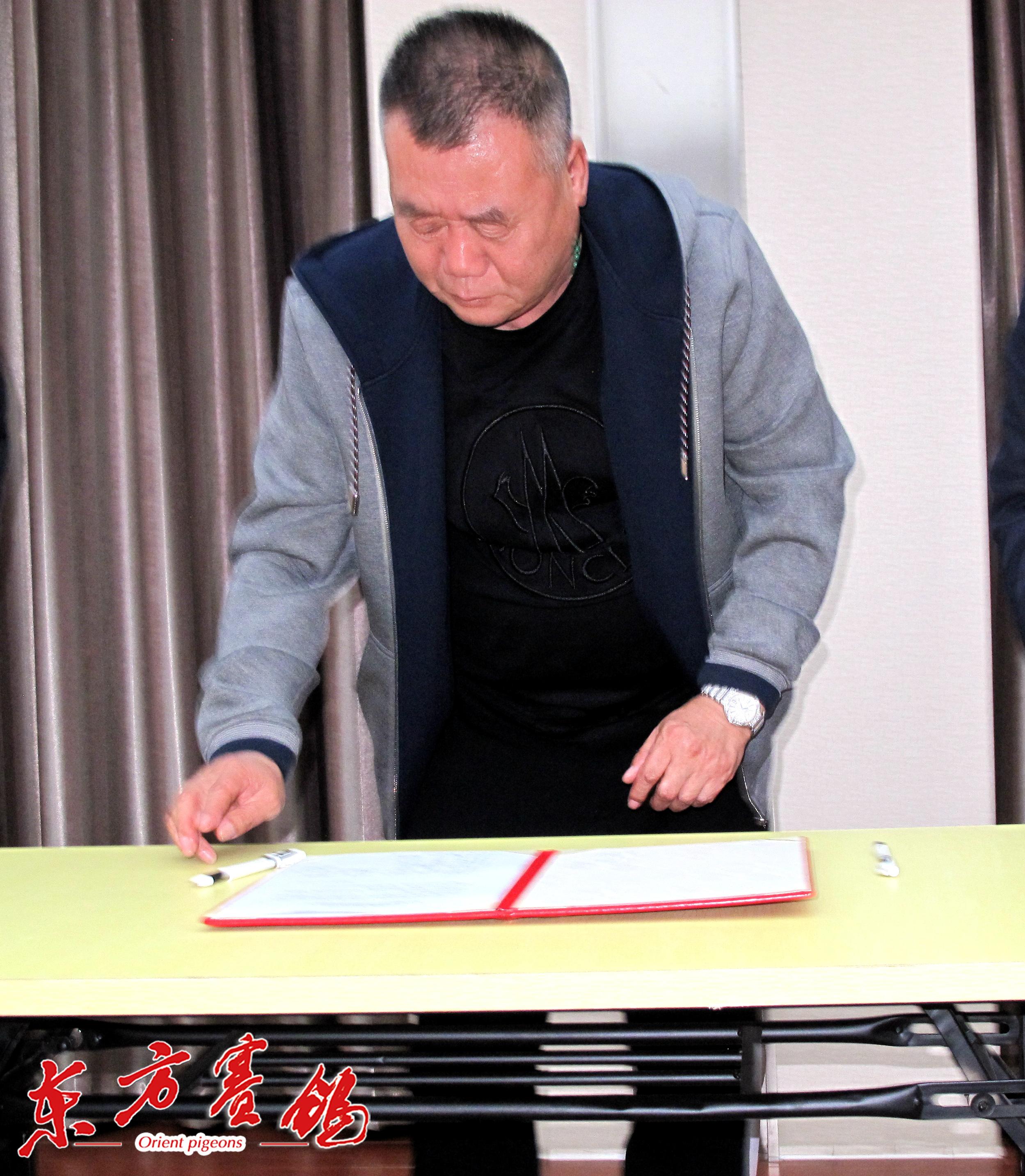 19、天津滨海新区鸽协秘书长刘为民在打击网鸽活动协议书上签字。