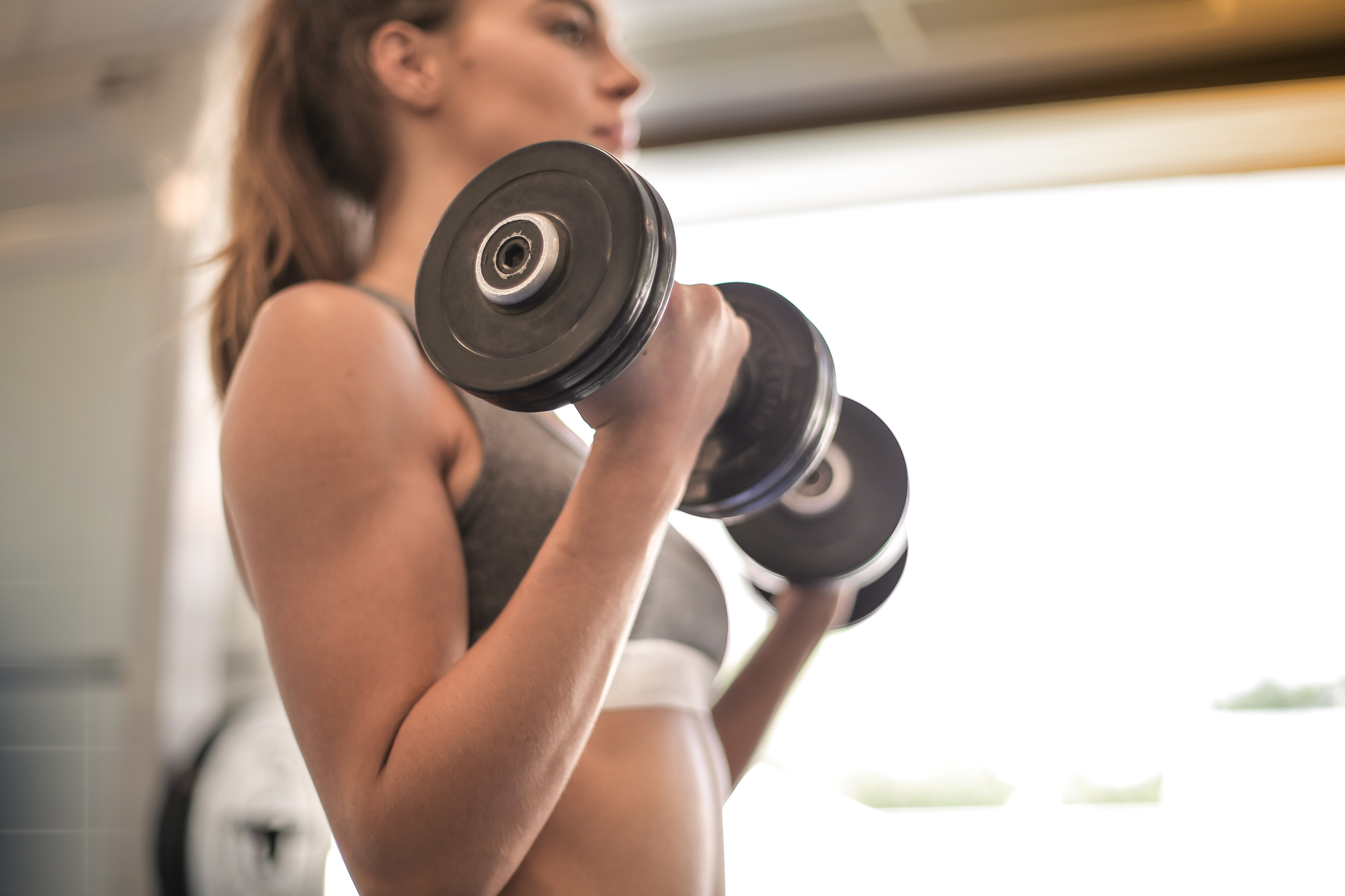 woman-in-gray-sports-bra-holding-black-dumbbell-3757376