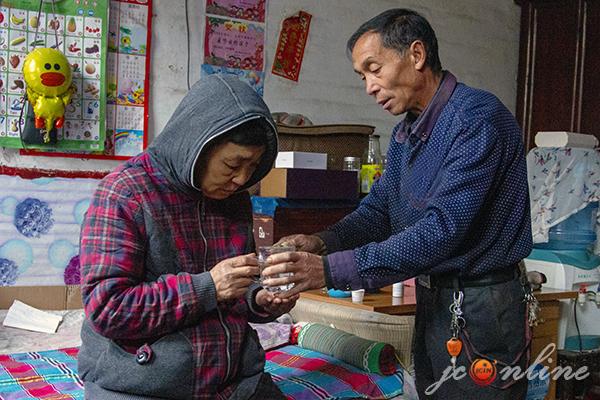 刘喜成在照顾妻子吃药