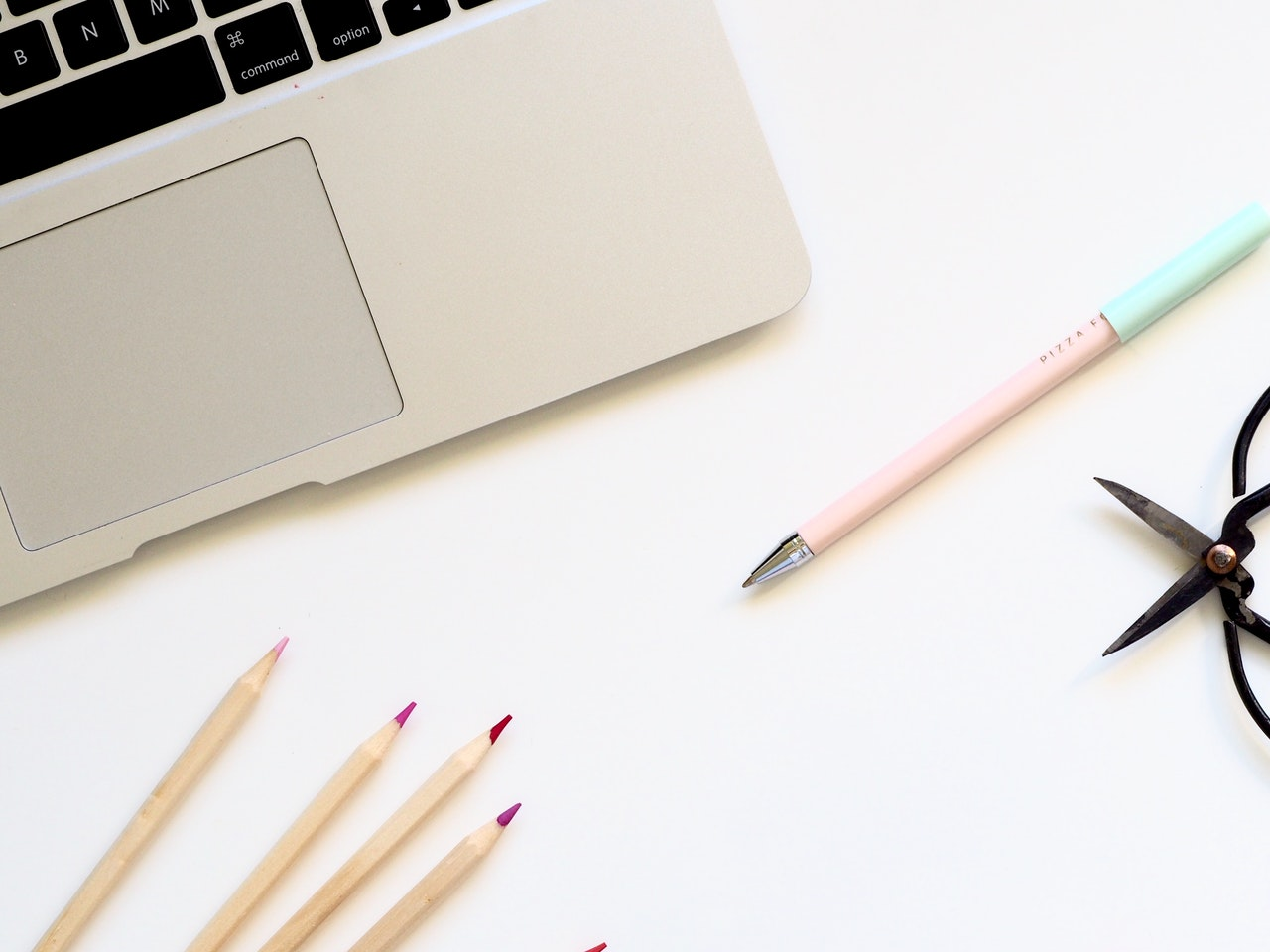 macbook-pro-and-pink-pen-on-table-1007026